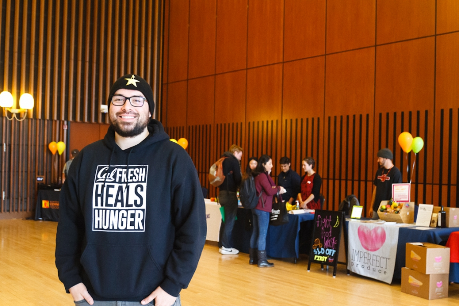 Man standing in auditorium in front of tables, in CalFresh sweatshirt