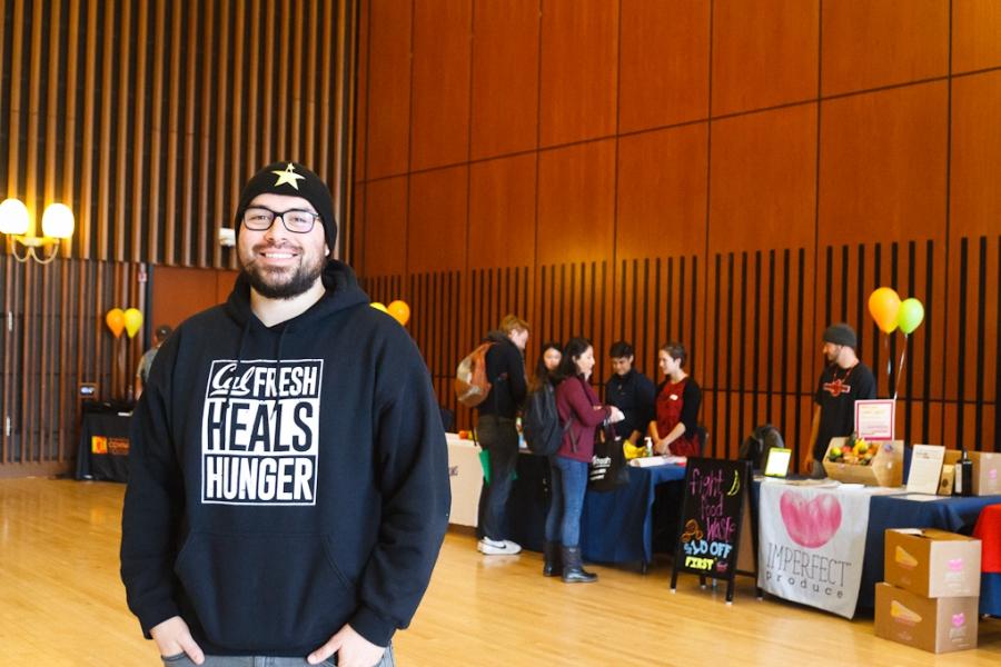 Man standing in auditorium in front of tables, in CalFresh sweatshirt