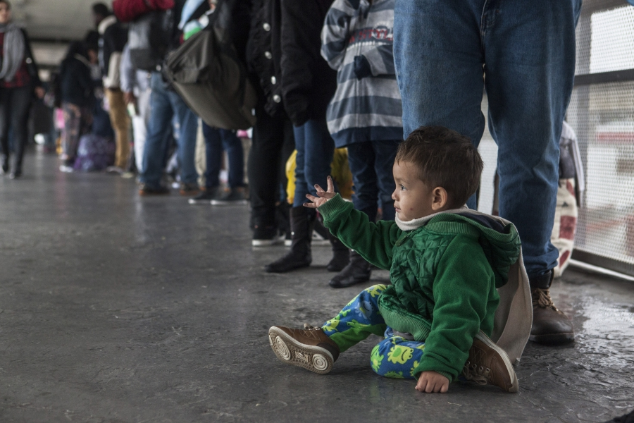 A young Central American boy sits while waiting in the line of asylum seekers who turned themselves in at the U.S. border on Sunday, May 7, 2017.