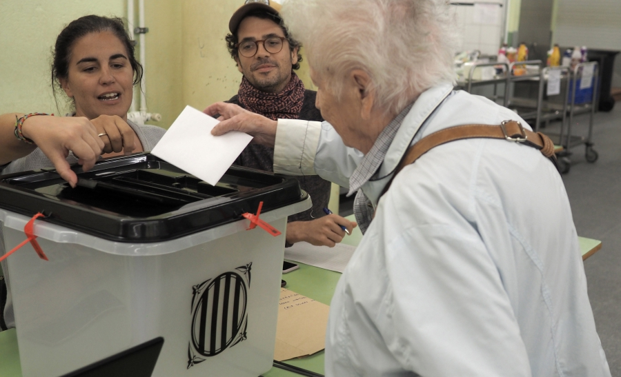 A voter partakes in a risky endeavor: casting a ballot in Catalonia's outlawed referendum for independence from Spain.