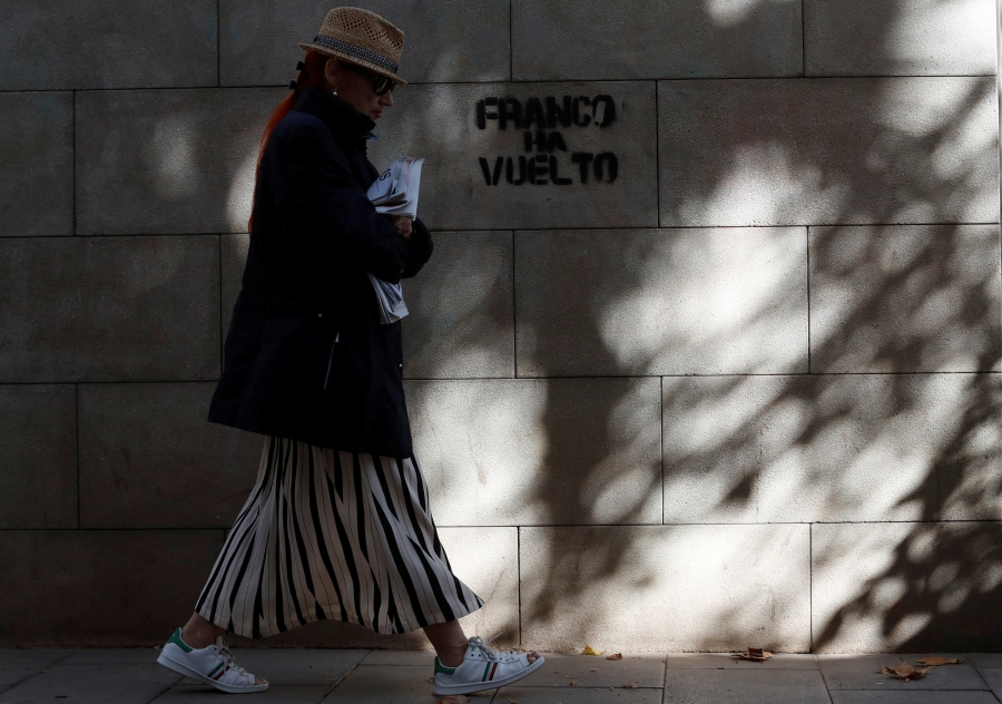 "A woman walks past a graffiti which reads ""Franco is back"" in Barcelona."