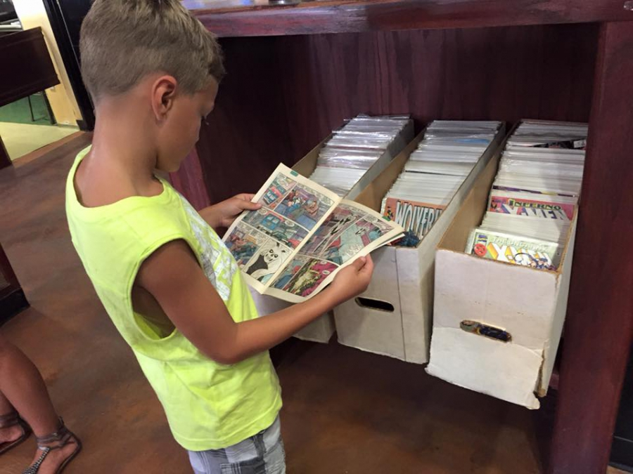 A child peruses comic books at Chicano-Con