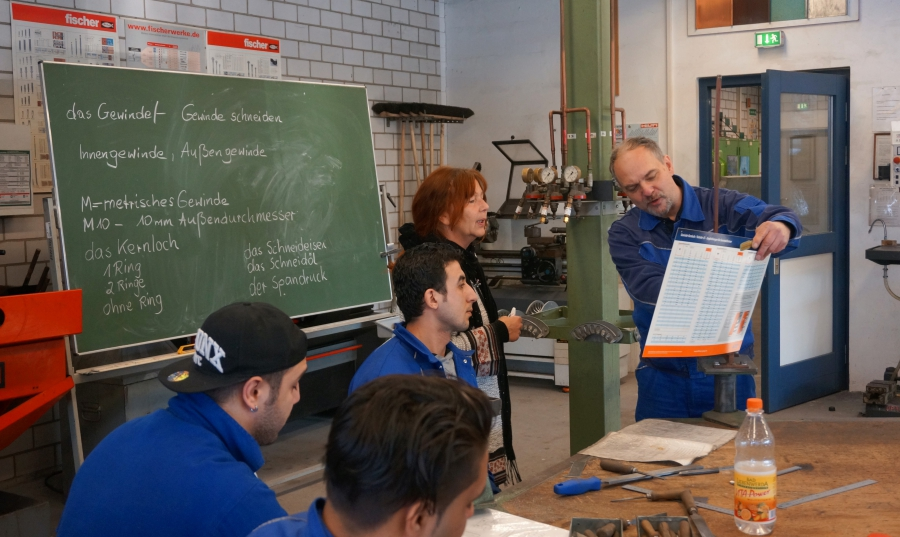 Instructor Gerald Bayer discusses the day's assignment with the class German instructor. As Bayer gives the day's lesson in metalwork, relevant vocabulary is written on the chalkboard. It's a crucial step in getting the refugee participants' language up t