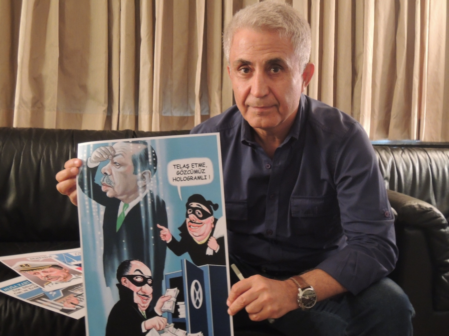 Photo of Turkish cartoonist Musa Kart holding a cartoon that prompted a law suit from President Erdogan who charged the cartoonist with insult and slander. The cartoon depicted the Turkish president as a hologram keeping a watchful eye over a robbery. Kar