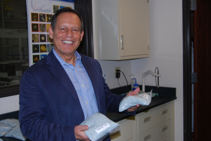 CarbonLITE Ceo Leon Farahnik holds bags of plastic pellets made from old bottles. CarbonLITE sells these pellets to bottle manufacturers.