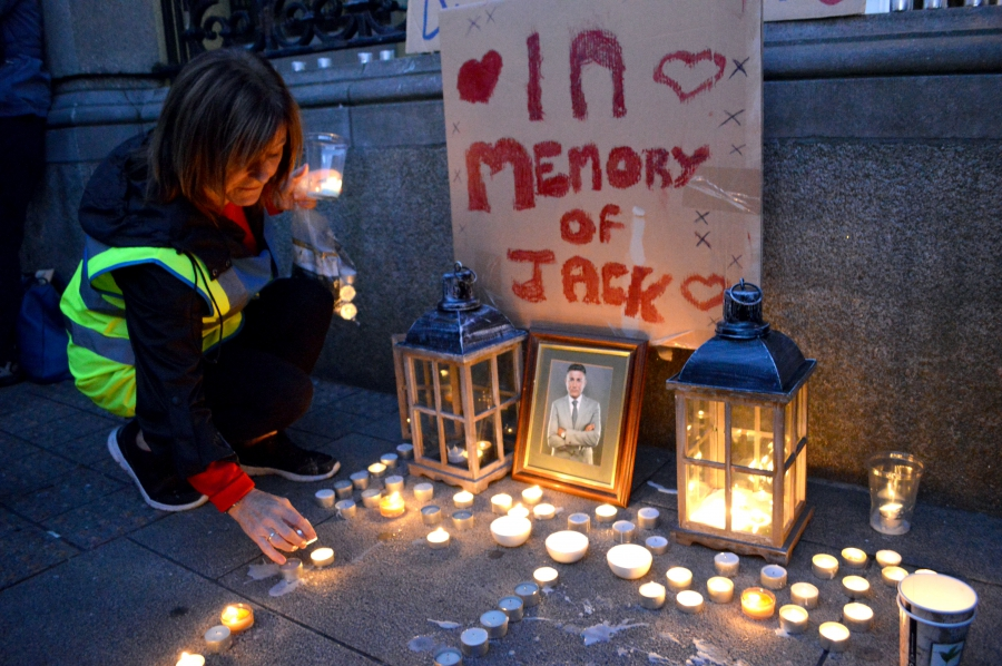 woman lighting candles at a vigil of a homeless man