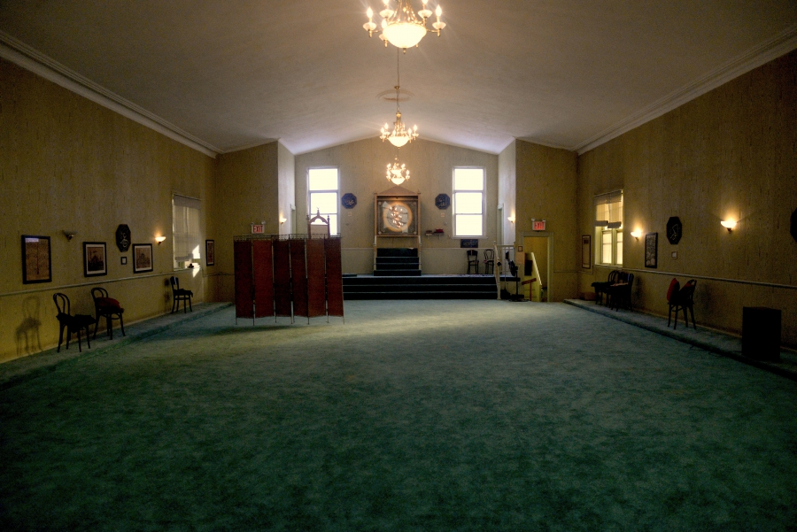 Main room of a mosque, with green carpet and a platform at front