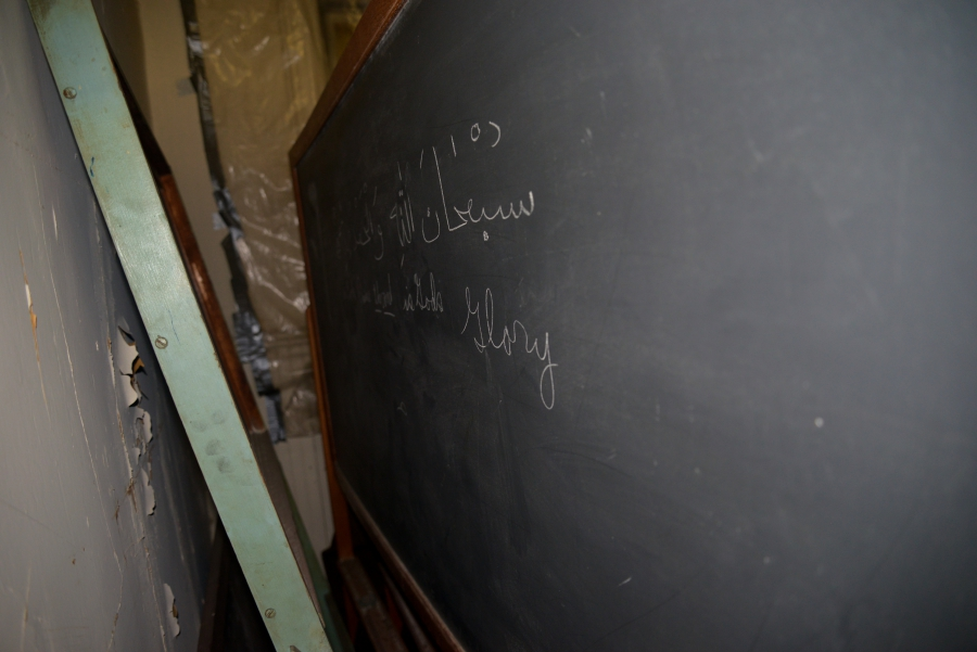 Old chalkboard with writing in Arabic and English