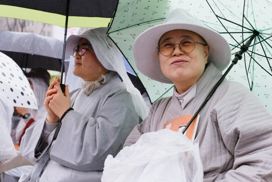 Buddhist nuns, along with monks and laypeople, tried to stay dry at this year's annual public reading of the Diamond Sutra in downtown Seoul.