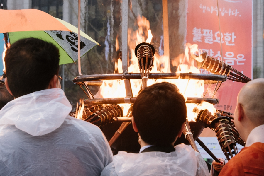 Buddhist monks and political officials lit torches at a public event for reciting the Diamond Sutra in downtown Seoul on April 5, 2017.