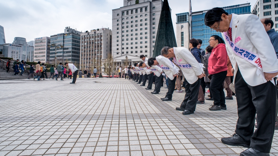 Ushers outside of a recent Sunday service at Yoido Full Gospel Church bow as worshippers begin to leave the church.