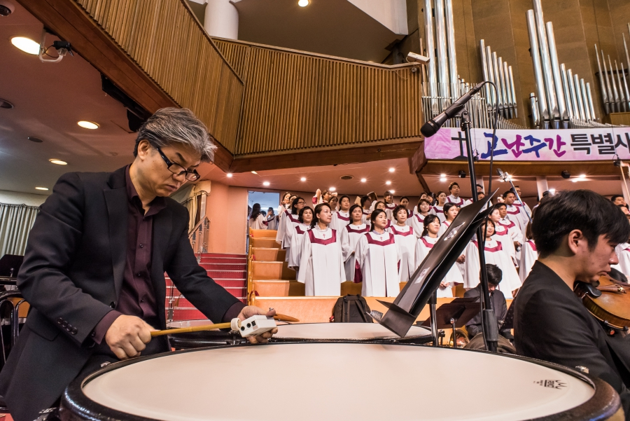 The message at Yoido Full Gospel Church is about faith, the Bible, and prosperity. The music is provided by a professional choir and a full orchestra.