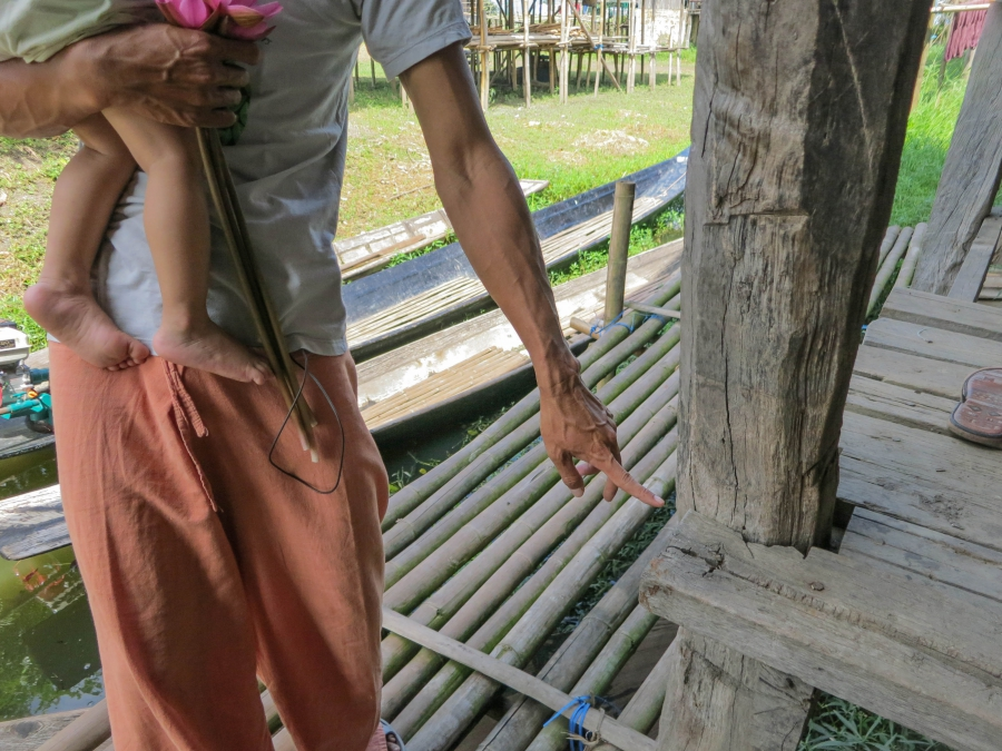 Activist Kyaw Soe points to the level on his house which Inle Lake's water used to regularly reach. Like most here, the house was built on stilts and used to stand above open water most of the year. Now, he says, it's on dry land most of the year.