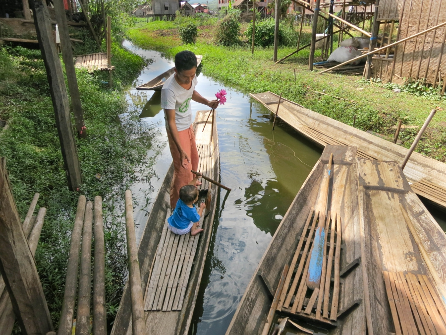 Kyaw Soe and his son Lone Lone play at paddling in a canoe outside their home on the edge of Inle Lake.
