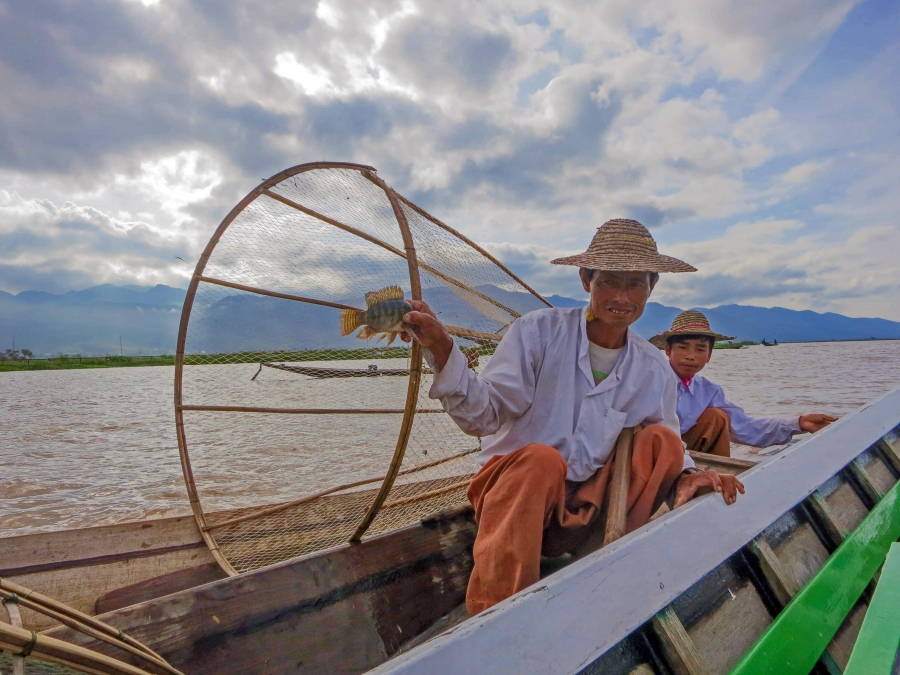 A fisherman holds up the already-dead fish that he used in his performance for tourists. With pollution and other human impacts harming Inle's aquatic ecosystem, the man now makes much more money performing his fishing routine than actually fishing.