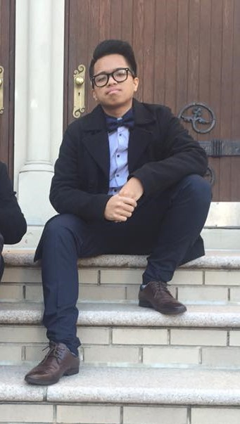 Young man sits on steps of a building