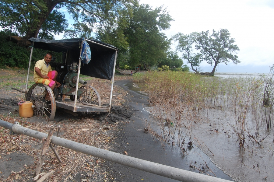 Ometepe farmer Dayton Guzman fixes his irrigation pump on the shore of Lake Nicaragua. Surveyors recently showed up on his farm representing a company that wants to build a hotel related to the canal project. Guzman says he and his family don't want to se