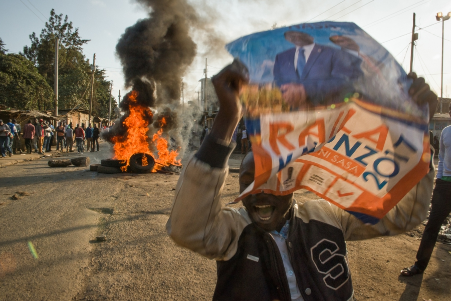 A man holds a campaign sign for presidential candidate Raila Odinga of the opposition party in the Kibera neighborhood of Nairobi, Kenya. Protesters were demanding that current President Uhuru Kenyatta concede to presidential candidate Raila Odinga of the