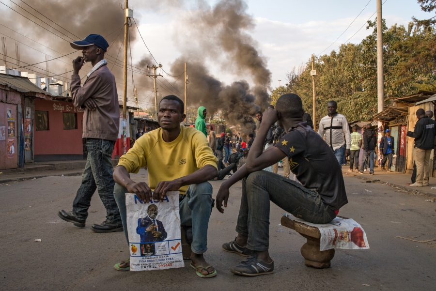 Men watch demonstrators light tires on fire in Nairobi's informal settlement of Kaibera. The demonstration quickly turned violent as demonstrators armed themselves with stones and clubs bearing nails Wednesday evening.