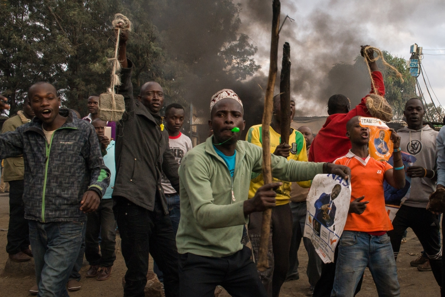 Men arm themselves with stones and clubs before clashing with residents in Kibera, an informal settlement in Nairobi, Kenya. The men supported presidential candidate Raila Odinga of the National Super Alliance over current President Uhuru Kenyatta.