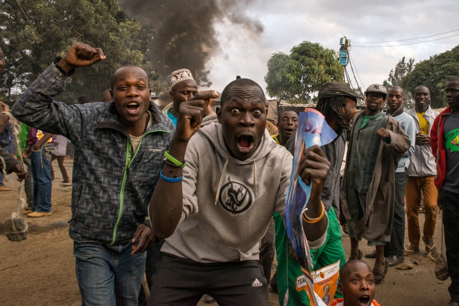 "Men yell ""Uhuru must go!"" during a demonstration in Kibera, an informal settlement of Nairobi, Kenya. Many of the residents support Raila Odinga of the National Super Alliance over current President Uhuru Kenyatta."
