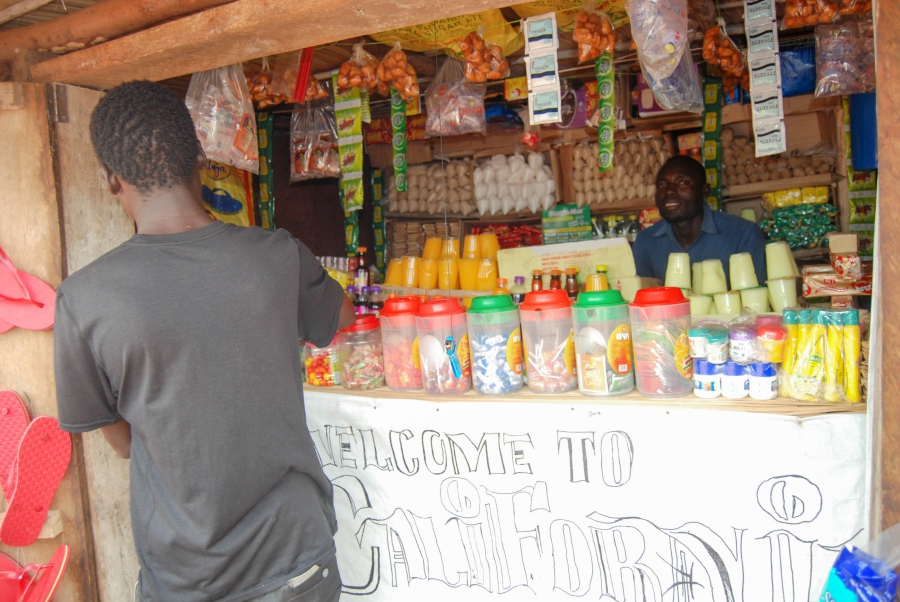 Nelson Doko sits behind the counter of his small shop in Uganda's Bidi Bidi refugee settlement. Business is slow, he says, since nobody has any money.