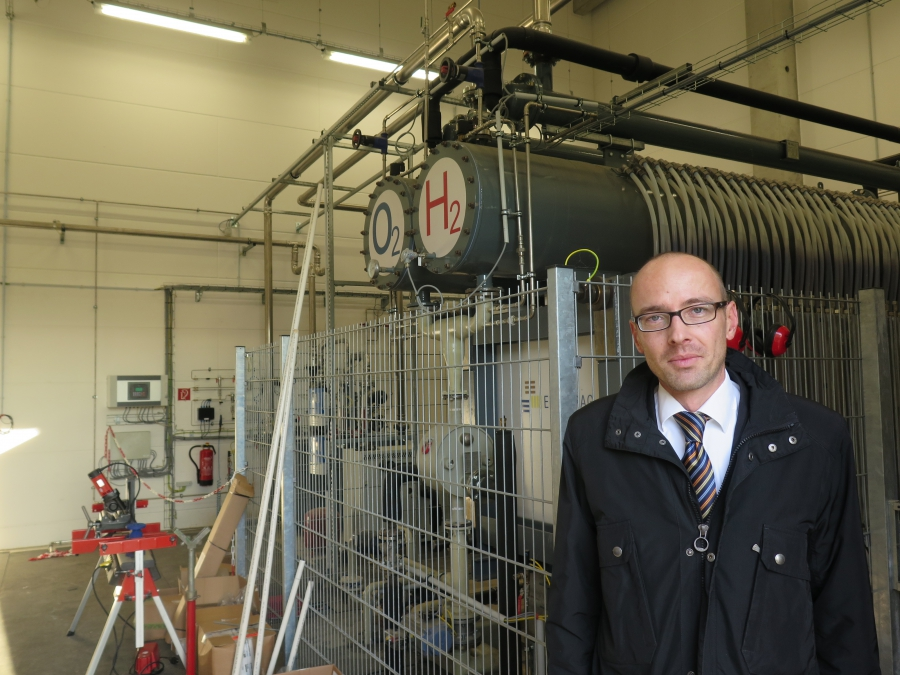 Enertrag's Robert During stands in front of his company's wind-powered electrolyser in Prenzlau, Germany. Electrolyzers use electricity to split water into hydrogen and oxygen. On this site, the oxygen is released into the air and the hydrogen is used as
