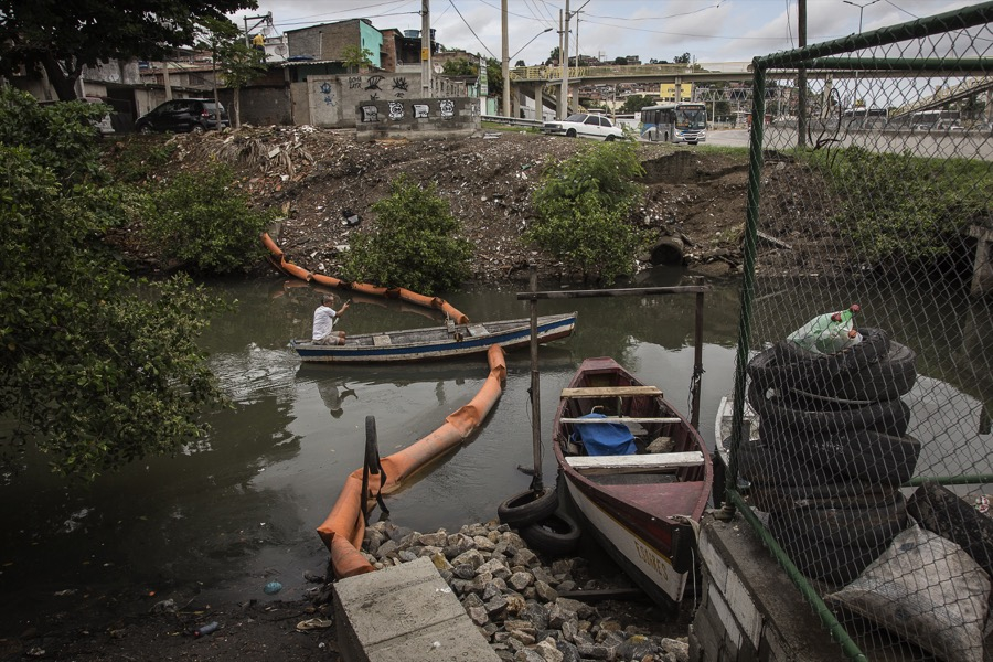 A fisherman rows through an eco-barrier that has been sliced in half on the Vila Maruí canal in the community of São Gonçalo in Rio de Janeiro.