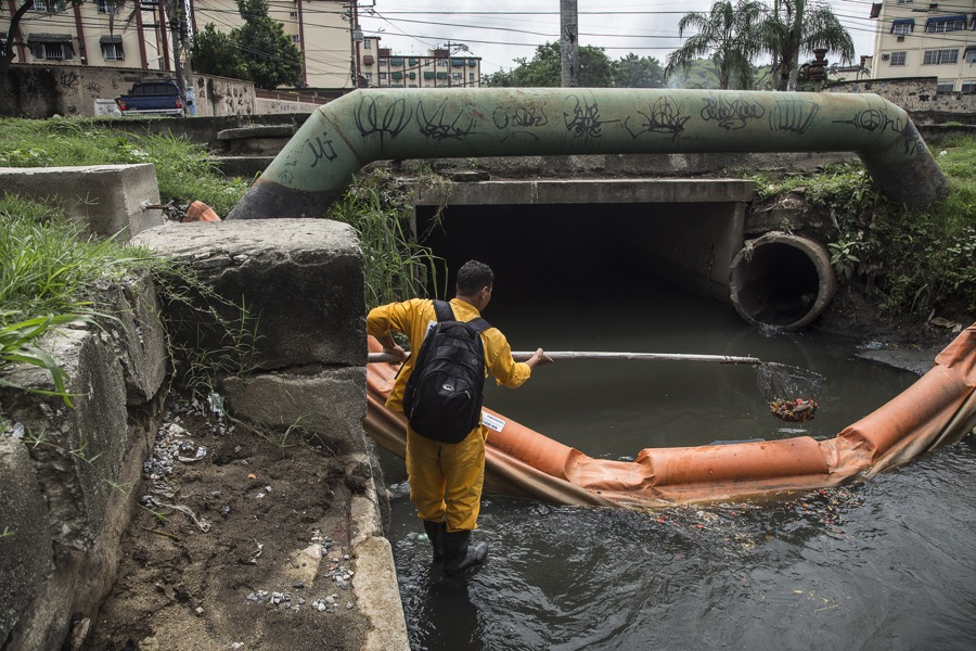 Marcelo Rocha, an employee of the Rio state environment institute, collects trash from a canal in the São Gonçalo neighborhood.