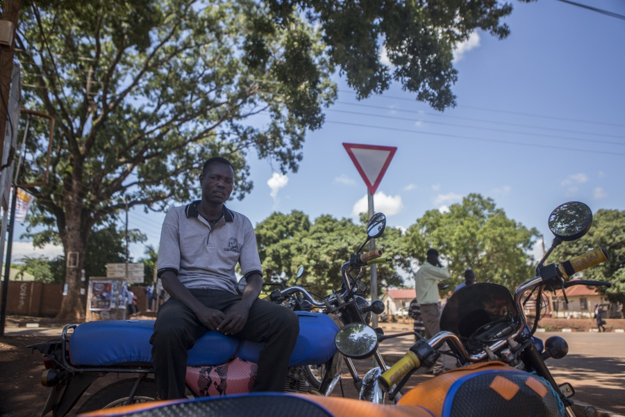 Kenneth Banya rests at the motorcycle taxi stop.