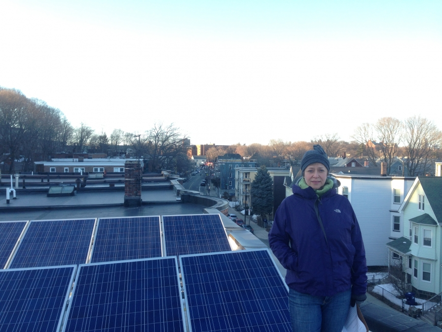 Edith Buhs, with the solar panels she recently installed on the roof of her Boston building. The electricity from the system supplies about half of the needs of the building's three apartments, but most of it flows first onto the electric grid. It's a sys