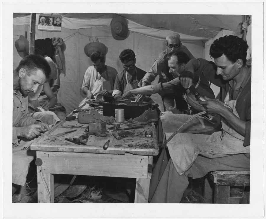 Men work around a table in a tent