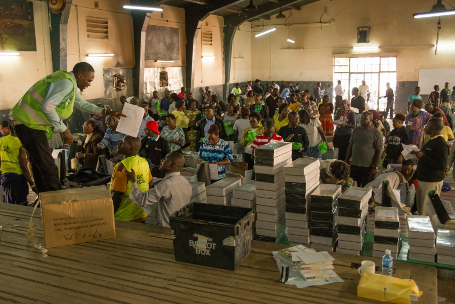 Officials with Kenya's Independent Electoral and Boundaries Commission distribute ballots and vote tallying forms to polling station officers before Tuesday's presidential election.