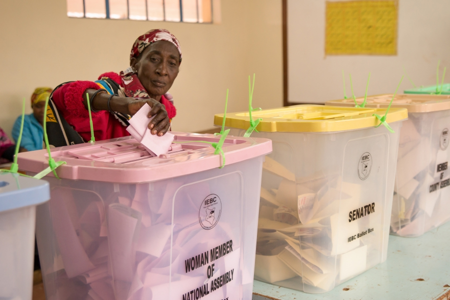 An elderly woman submits her ballot at Kibera Primary School in Nairobi. Many voters withstood long lines and slow registration technology to vote in Tuesday's elections.
