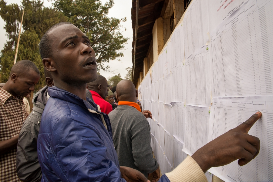 A man from an informal settlement in Nairobi searches for his name on a voter registration list at Kibera Primary School. Some voters were unable to locate their names on the registrar, forcing them to contact election officials for assistance.