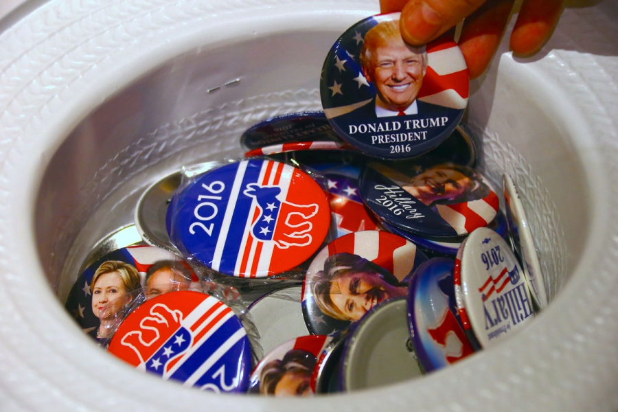 A guest at an event called the US Presidential Election Watch reaches for a badge from out of a hat displaying photographs of Republican candidate Donald Trump and Democratic candidate Hillary Clinton, in Sydney.