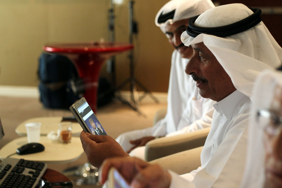 A trader uses his smartphone to follow news of the US presidential elections as he monitors a screen displaying stock information at Qatar Stock Exchange in Doha.