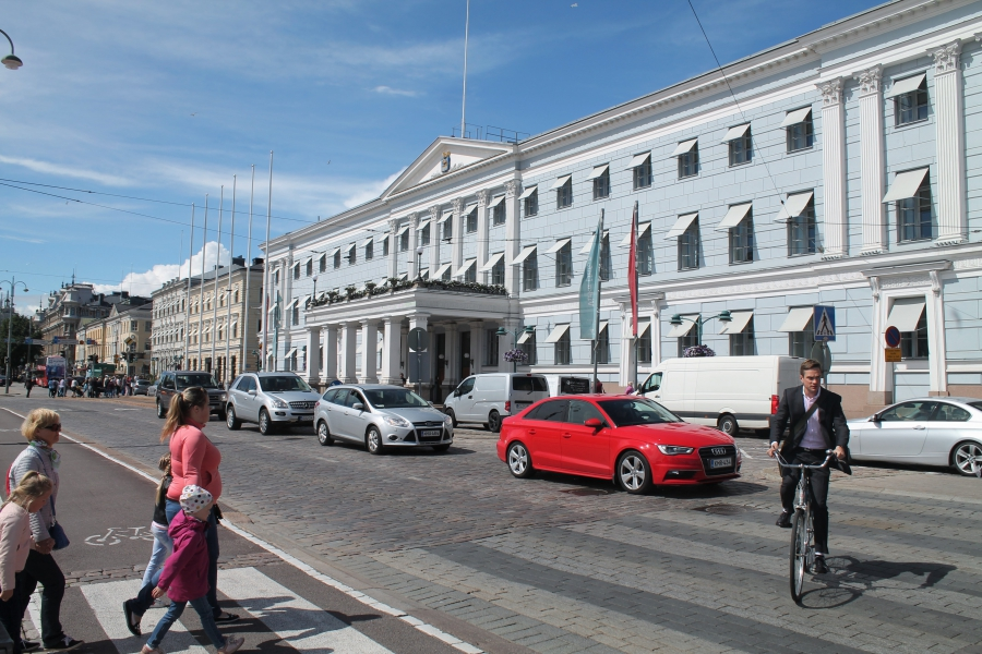Cyclists, pedestrians and cars coexist outside Helsinki City Hall.