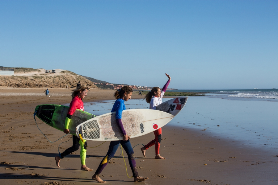 Ghita Guemmi (right), and Fatima Berrada (left), Lilias Tebbaï (center) approach the water with their surfboards.