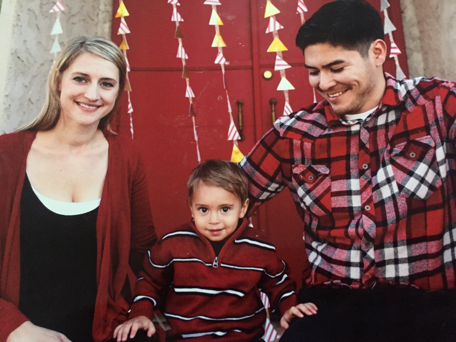 Family photo, with woman and young toddler smiling for camera and man looking at child, smiling. All in red or red plaid.