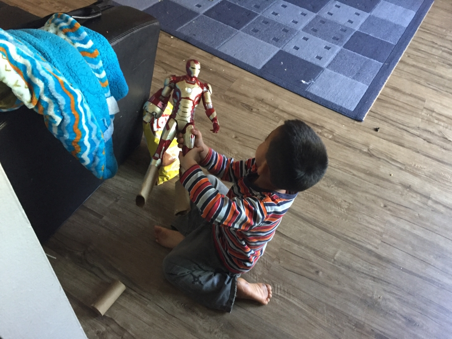 Boy sitting on floor playing with action figure