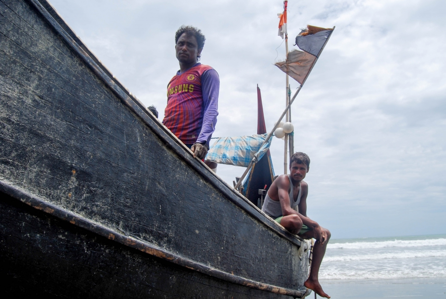 Aman Ullah, left, a Rohingya refugee in Cox's Bazar, takes home one-tenth of the profits that his fishing boat makes every day. The rest goes to the boat's owner and his four other crewmates.