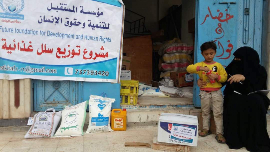 In Aden, Yemen, children stand outside the door to a warehouse beside bags of food readied for donation to the poor.