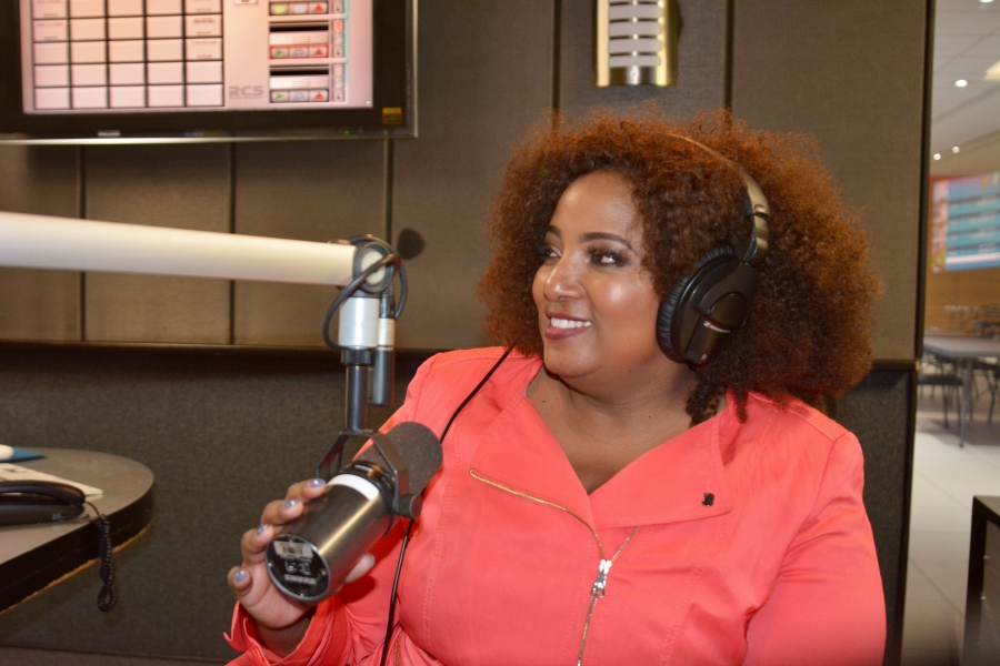 Sex talk radio host Criselda Kananda Dudumashe sitting in front of a microphone with headphones on.