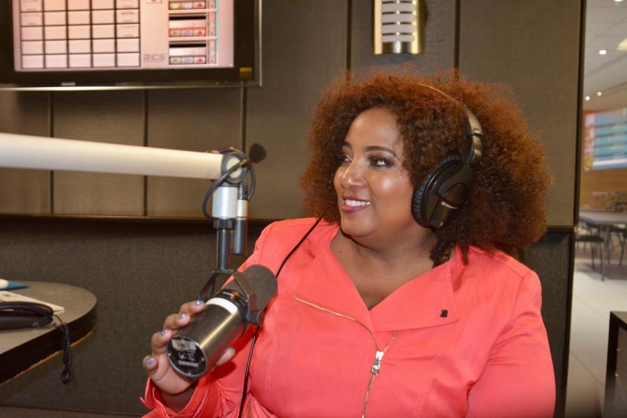 Sex talk radio host Criselda Kananda Dudumashe sitting in front of a microphone with headphones on.