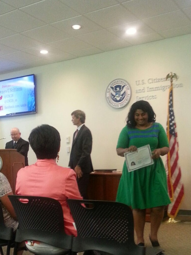 Blurry image of Koshy in front of USCIS sign and seal, with her citizenship certificate