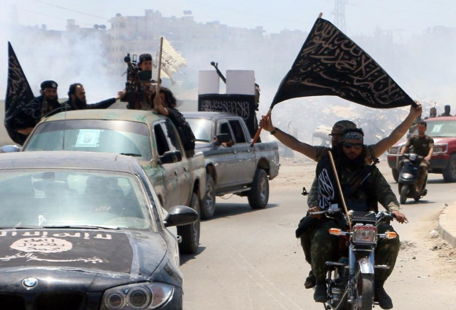 Fighters from Al Qaeda's Syrian affiliate Al-Nusra Front in the northern Syrian city of Aleppo flying Islamist flags as they head to a frontline on May 26, 2015.