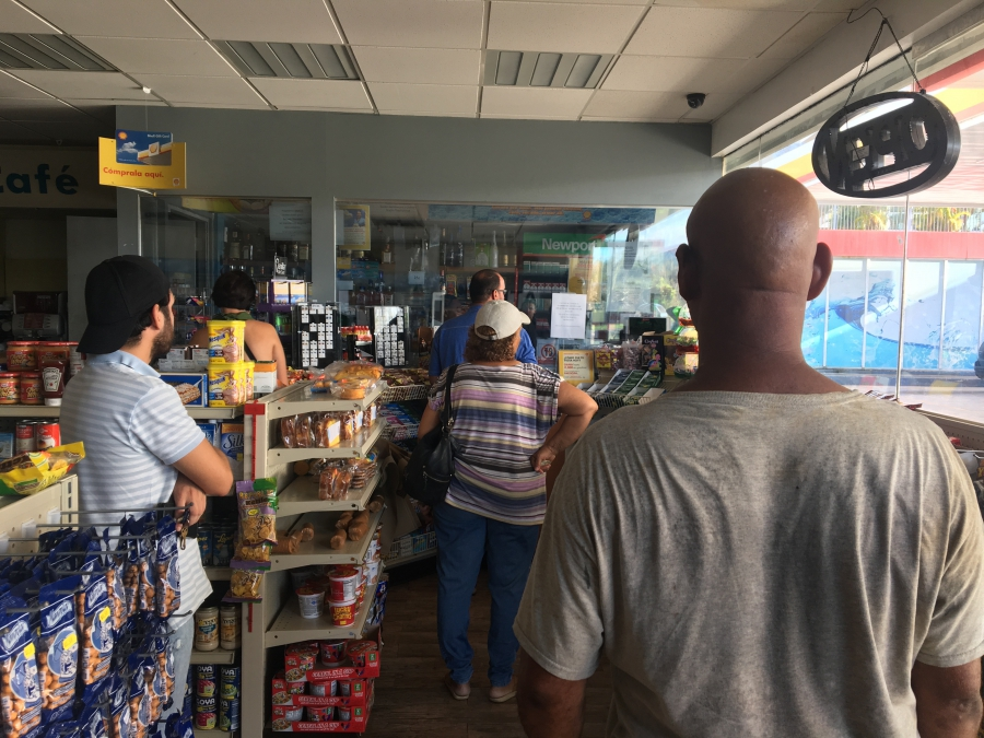 A line of people waiting in a gas station in San Juan, Puerto Rico.