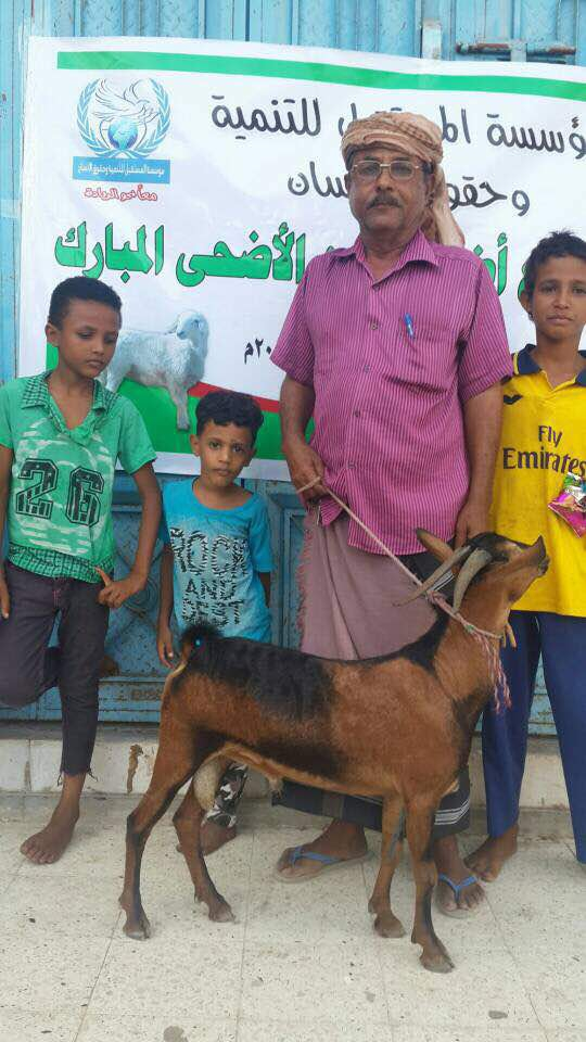 A man in Aden, Yemen, holds tight to the leash of a goat.