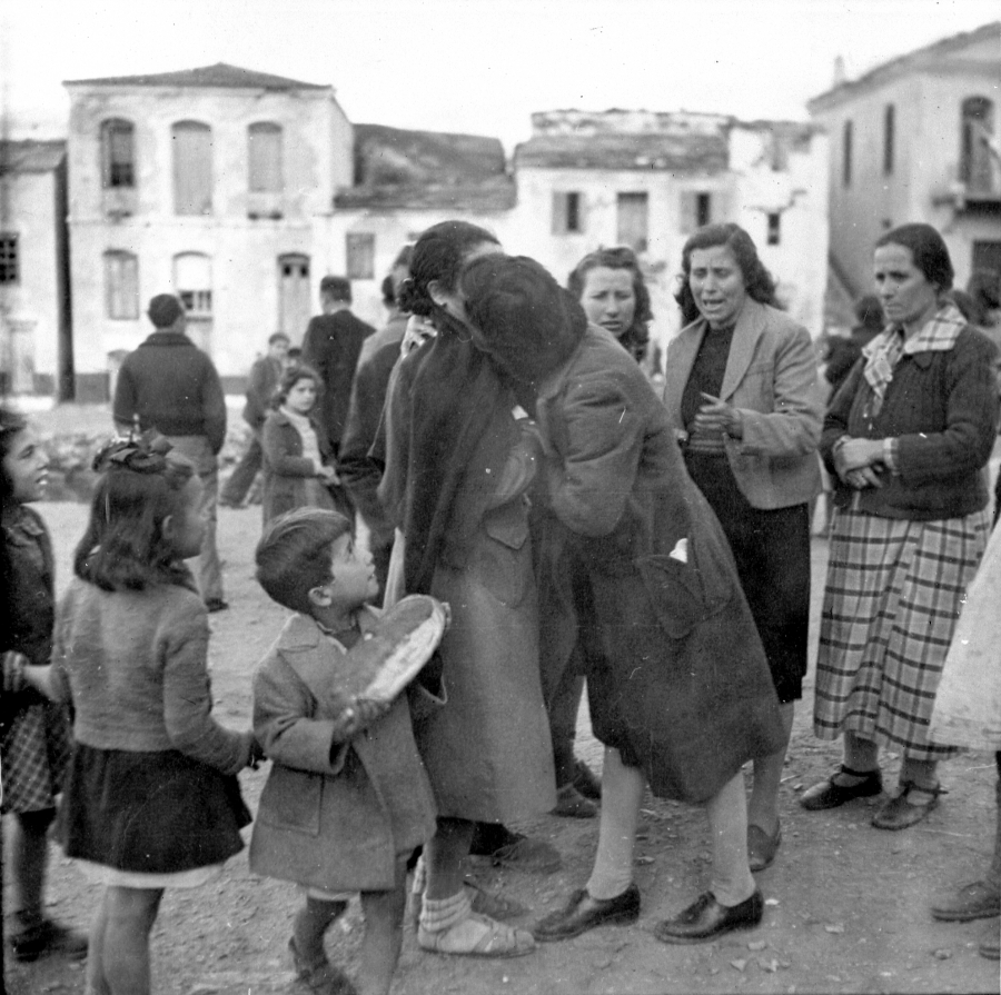Two women hug while children look on, and other women look on crying. In black and white